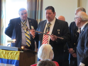 Outgoing President Marty Shipe (center)presents the Admiral Reynold T Hall, USN honorary saber to the newly elected SJC President Harry Engleman, Jr. New Jersey Society SAR President (left) Clark McCullough looks on.